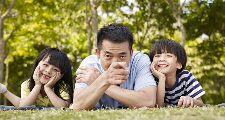 Asian father lying on lawn with son and daughter, pointing at camera