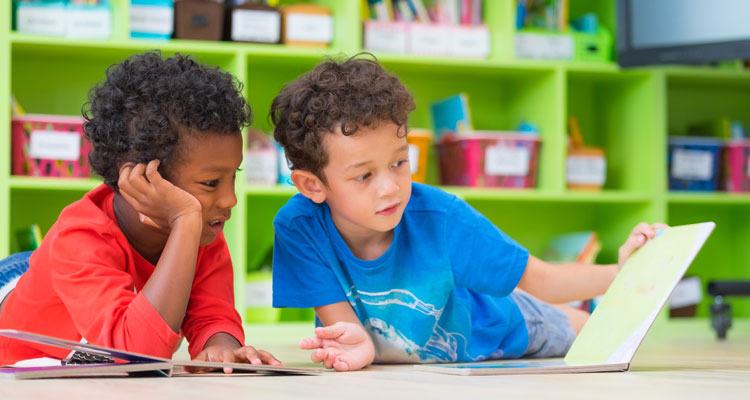 Two young boys on floor, reading book in preschool library