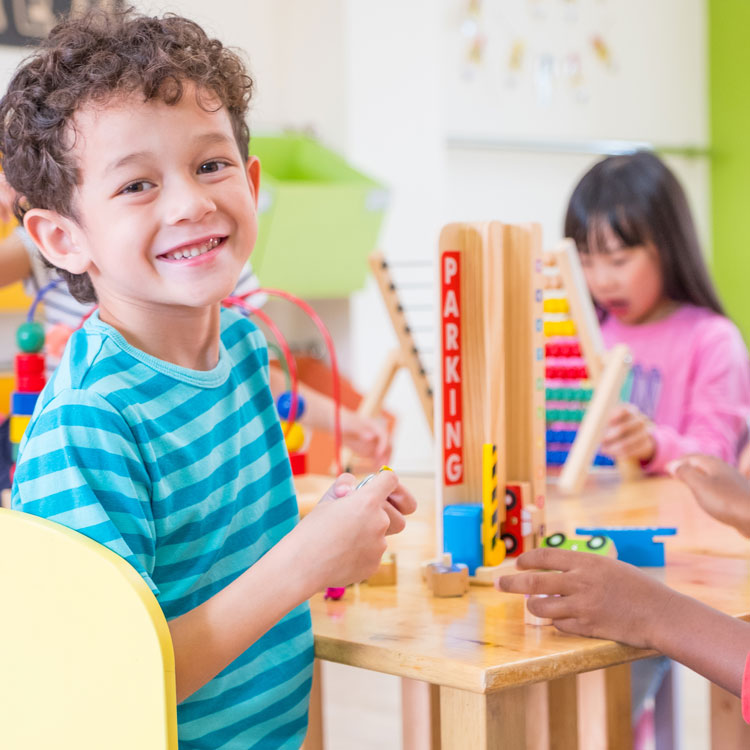 Smiling young boy playing with blocks in daycare
